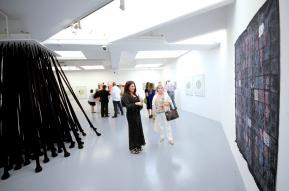 Amira Ali Behbehani presenting her artwork to exhibition visitors